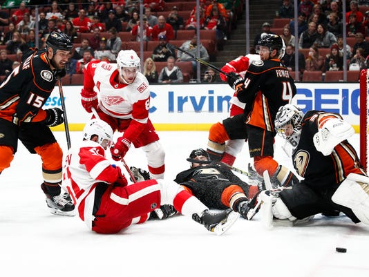 Players are tangled up as Anaheim Ducks goaltender John Gibson makes a save during the first period of an NHL hockey game against the Detroit Red Wings Friday, March 16, 2018, in Anaheim, Calif. (AP Photo/Jae C. Hong)