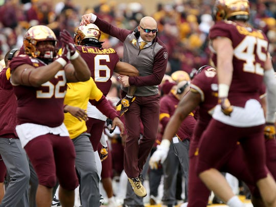 Minnesota head coach P.J. Fleck, center, jumps in celebration with defensive back Chris Williamson after the defense stopped the ball against Penn State during an NCAA college football game Saturday, Nov. 9, 2019, in Minneapolis. Minnesota won 31-26. (AP Photo/Stacy Bengs)
