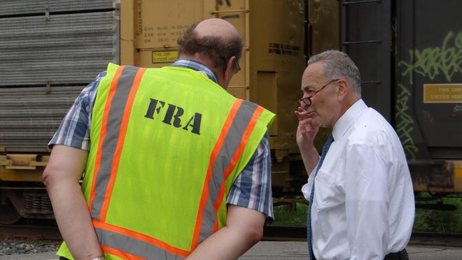 U.S. Sen. Charles Schumer talks with Federal Railroad Administration supervisory specialist Robert Winstel at a railroad crossing in Chili following a June 15 news conference.