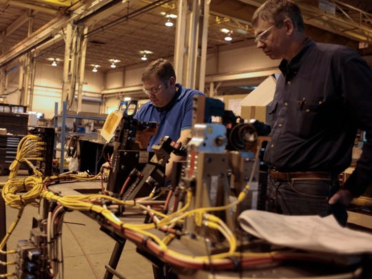Steve Corbat, left, from Fraser and John Schuler from Saline inspect components before they are placed into a weld cell on Dec. 12, 2014 at The Paslin Company in Warren. Michigan's jobless rate now matches the national average for the first time in 15 years.