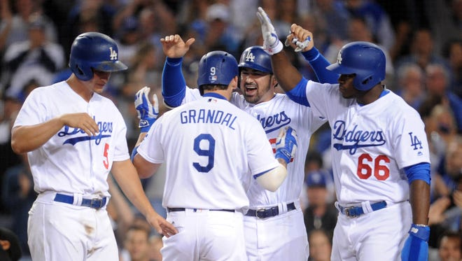 Dodgers catcher Yasmani Grandal (9) is greeted by Corey Seager (5), Adrian Gonzalez (23) and Yasiel Puig (66) after hitting a grand slam in the seventh inning.