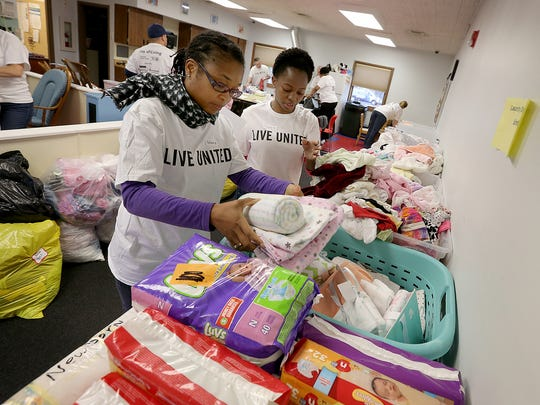 Here Stacy Christie (left) and Taffy Nyatoti help organize and pack starter bags for mothers in need for newborn baby supplies.