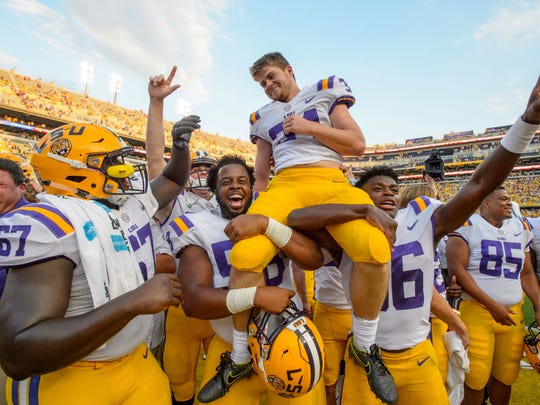LSU head coach Ed Orgeron, left, smiles as place kicker Connor Culp (34) is lifted on the field by teammates Jibrail Abdul-Aziz (58) and Cameron Gamble (36) after kicking the winning field goals in their 27-23 victory against Auburn in an NCAA college football game in Baton Rouge, La., Saturday, Oct. 14, 2017.