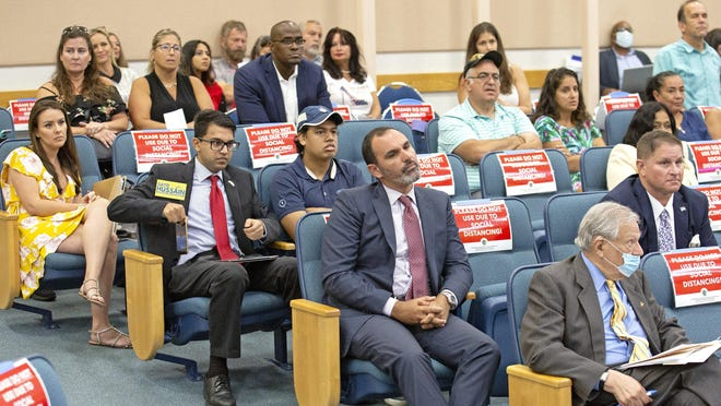 A group of maskless opponents of the the wearing of masks sit in the audience at the Palm Beach County Commission meeting June 23 where commissioners unanimously voted to require people to wear masks in public.