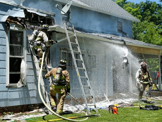 Firefighters bring a house fire under control Friday, June 13, 2014, at 103 E. Oak Street in West Lafayette. Homeowner Michael Poling said he accidentally started the fire when he was removing paint with a heat gun. There were no injuries.
