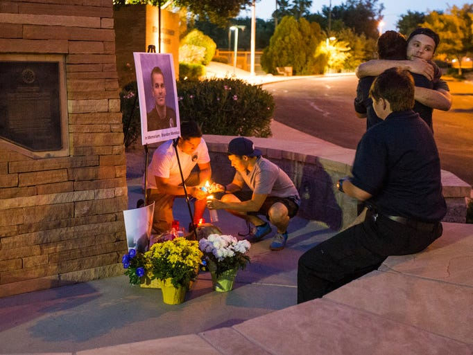 Mourners pay their respects at a makeshift memorial for Mesa police Officer Brandon Mendoza outside the Mesa Police Department headquarters Monday (May 12, 2014). Mendoza was killed early in the morning by a driver who drove more than 30 miles in the wrong direction on Valley freeways before colliding head-on with the officer near the U.S. 60 interchange with Interstate 10 in Tempe.