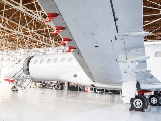 A JetSuiteX Embraer ERJ135 jet inside a hangar.