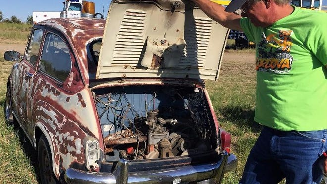 Shane Hegle of Rustless in Montana shows the engine of a 1967 Fiat at the Rustless in Montana yard east of Cut Bank.