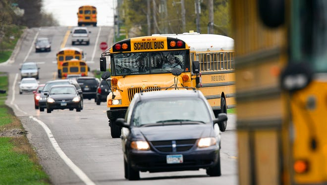 Cars and busses maneuver on Stearns County Road 136 as school lets out Wednesday, April 27, outside Oak Hill Community School.