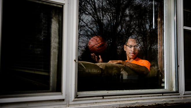 Former Waverly Girl's Basketball Head Coach ,T.J. Hawkins, looks out the front window at his home in Lansing Thursday January 19, 2017.   Hawkins suffered a stroke that forced him to leave his Waverly coaching position and is struggling to recover and regain a coaching position.  The stroke has left him with limited vision so he is not allowed to drive often leaving him alone at home. KEVIN W. FOWLER PHOTO