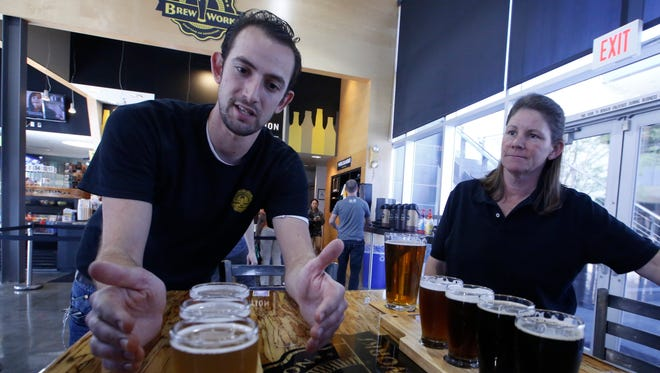 In this Thursday, March 19, 2015, photo, Koby Harris, brewery production manager, left, and Sandra Cain, assistant director of retail operations, present their freshly brewed beers at Innovation Brew Works in the California State Polytechnic University, Pomona in Pomona, Calif. Although the beer made on Pomona's campus is sold at the university's pub, school officials say the effort isn't about providing product for boozy frat boys. It's about responding to a booming craft-beer market by giving students the skills to compete for jobs in a rapidly expanding section of the hospitality industry. (AP Photo/Damian Dovarganes)