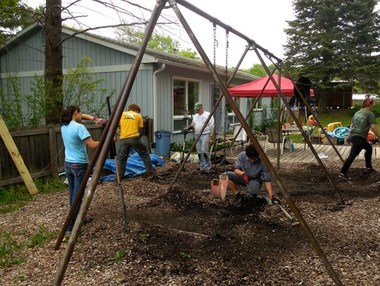 Workers gather to refurbish the playground at the Ellis