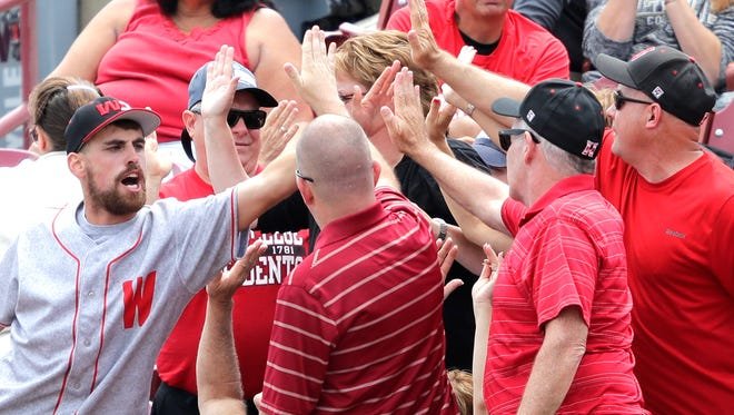 Washington & Jefferson College fans celebrate scoring a run against Concordia University Friday during the NCAA Division III Baseball Championships at Fox Cities Stadium in Grand Chute.