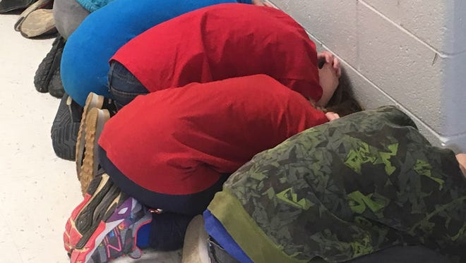East Heights students take cover as part of a school-district tornado drill Friday morning.