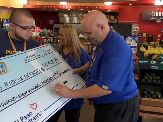 Chris Frechette, store manager of the Corner Store at Zaragoza and Tierra Este roads in far East El Paso, signs a check for the $75,813 raised in April by 43 El Paso Corner Stores for the Children's Miracle Network to benefit El Paso Children's Hospital.