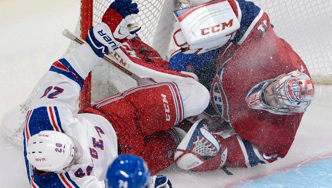 New York Rangers left wing Chris Kreider (20) crashes into Montreal Canadiens goalie Carey Price, right, during the second period in Game 1 of the Eastern Conference finals in the NHL hockey Stanley Cup playoffs against in Montreal on Saturday, May 17, 2014.