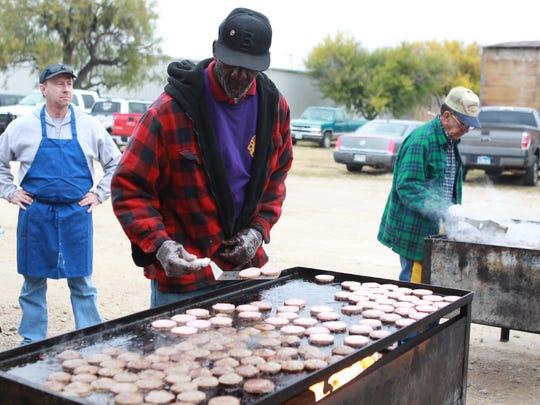 Volunteer John Thomas cooks sausage patties behind