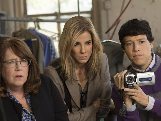 "Ann Dowd, from left, Sandra Bullock and Reynaldo Pacheco are seen in a scene from ""Our Brand Is Crisis."""