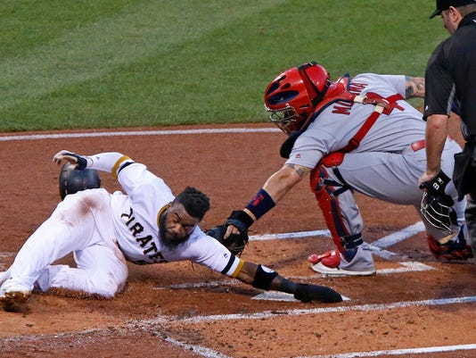 Pittsburgh Pirates' Josh Harrison, left, scores around the tag of St. Louis Cardinals catcher Yadier Molina, center, with umpire Chris Conroy, right, watching the play, during the first inning of a baseball game in Pittsburgh, Wednesday, Sept. 7, 2016. The Pirates won4-3. (AP Photo/Gene J. Puskar)