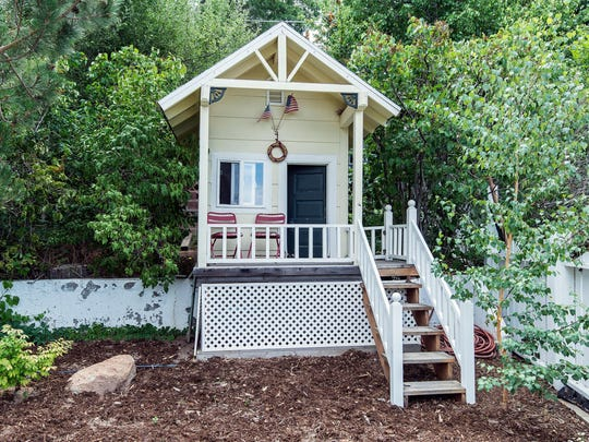 A bijoux playhouse (or dollhouse) occupies a corner of the backyard at 866 Skyline Blvd.