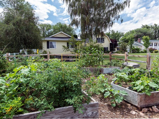 The front expanse of 866 Skyline Blvd. features a garden with a split-rail fence.