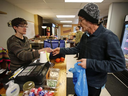 "In this Feb. 26, 2018 photo Dianne Shenk, left, helps a customer Terry Warby in Dylamatos Market in Hazelwood, Pa. About a quarter of Shenk's customers pay with benefits from the federal Supplemental Nutrition Assistance Program, so the government's proposal to replace the debit card-type program with a pre-assembled box of shelf-stable goods delivered to recipients concerns her and other grocery operators in poor areas. ""These boxes will be full of shelf-stable items, the same things we're being told not to eat,"" she said. (AP Photo/Gene J. Puskar)"
