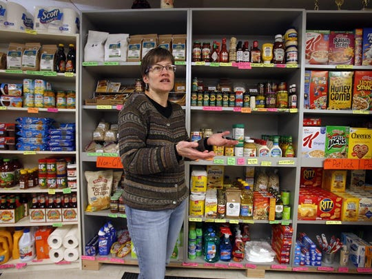 "This Feb. 26, 2018 photo shows Dianne Shenk talking to a customer in her Dylamatos Market in Hazelwood, Pa., Monday, Feb. 26, 2018. About a quarter of Shenk's customers pay with benefits from the federal Supplemental Nutrition Assistance Program, so the government's proposal to replace the debit card-type program with a pre-assembled box of shelf-stable goods delivered to recipients concerns her and other grocery operators in poor areas. ""These boxes will be full of shelf-stable items, the same things we're being told not to eat,"" she said. (AP Photo/Gene J. Puskar)"