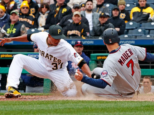 Minnesota Twins' Joe Mauer (7) scores on wild pitch ahead of the tag by Pittsburgh Pirates' Edgar Santana (37) during the sixth inning of the Pirates' home opener baseball game in Pittsburgh, Monday, April 2, 2018. (AP Photo/Gene J. Puskar)