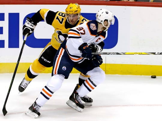 Pittsburgh Penguins' Sidney Crosby (87) defends against Edmonton Oilers' Connor McDavid (97) during the first period.