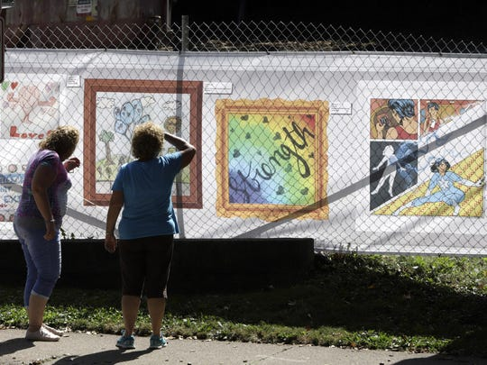 People look at art that is displayed on a fence surrounding the Tree of Life synagogue in Pittsburgh.