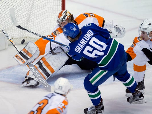Vancouver Canucks' Markus Granlund (60), of Finland, is stopped by Philadelphia Flyers' goalie Michal Neuvirth, of the Czech Republic, as Ivan Provorov, right, of Russia, defends during the first period of an NHL hockey game in Vancouver, British Columbia, on Sunday, Feb. 19, 2017. (Darryl Dyck/The Canadian Press via AP)