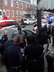 Residents of South Van Buren Street in Wilmington angrily confront officers making an arrest in the 400 block Wednesday afternoon. The residents, cussing and shouting at the officers, are angry at what they perceive to be the excessive allowance of a K-9 officer to bite a suspect while he was on the ground.