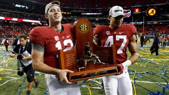 Alabama Crimson Tide quarterback David Cornwell and Christian Miller carry the trophy after the 2015 SEC Championship Game at the Georgia Dome.