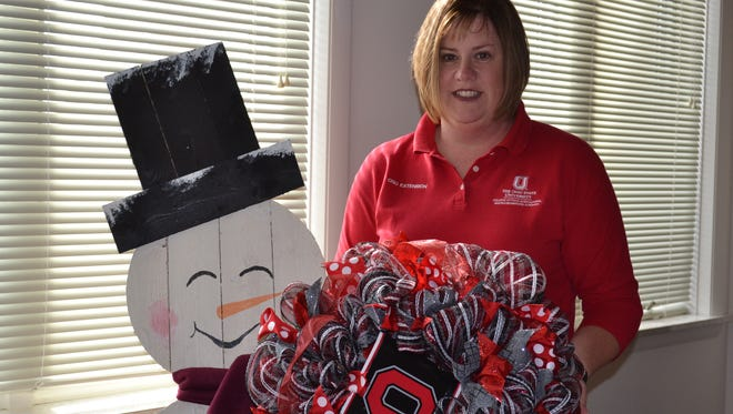 Shannon Castillo, office associate for the Ohio State University Extension office in Oak Harbor, with a couple of the over 200 auction items that will be available at the Cultivate the Clover dinner/auction on Saturday.