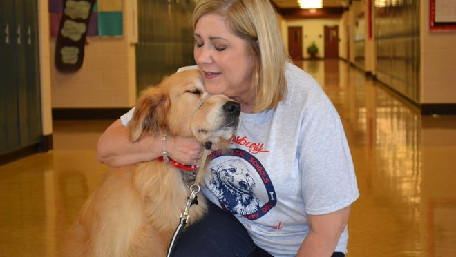 Nancy Slotterbeck snuggles with Lansbury, the only therapy dog trained by Assistance Dogs for Achieving Independence that was placed in a high school.