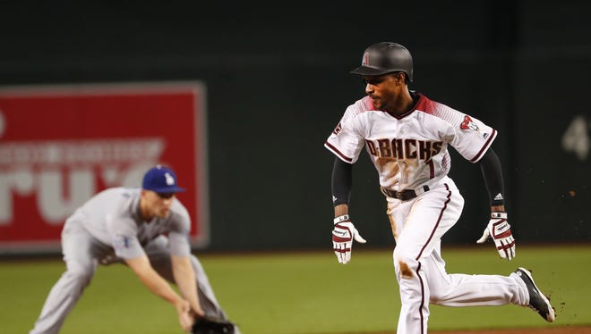 Arizona Diamondbacks center fielder Jarrod Dyson (1) takes third on a ground ball fielded by Los Angeles Dodgers shortstop Corey Seager (5) during the first inning at Chase Field in Phoenix April 4, 2018.