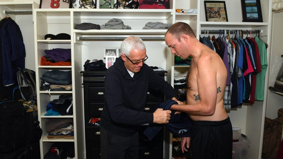 Tim's father, John, helps him get dressed.(Christopher Hanewinckel USA TODAY Sports Images)