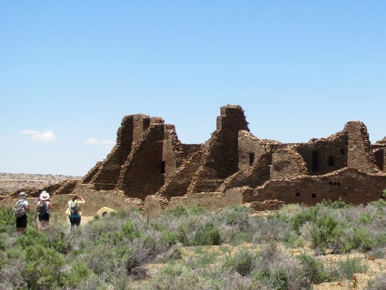 Visitors walk to an ancestral Puebloan ruin June 2013