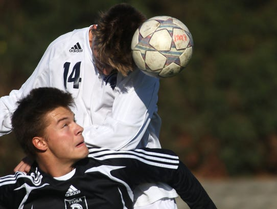 Brookfield East's Erik Solie (14) heads the ball away