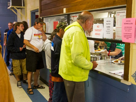 People line up to get food at Mid City Nutrition Tuesday,