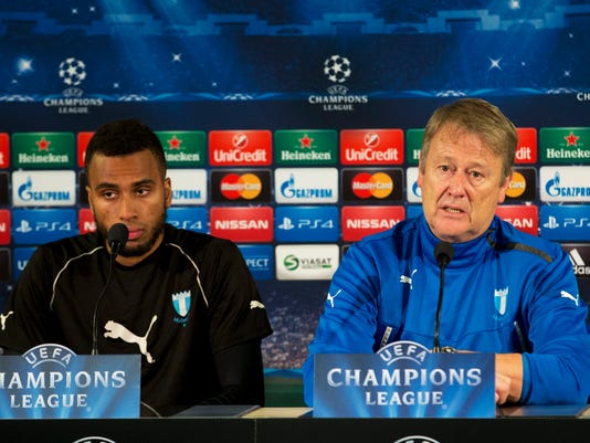 Malmo FF player Isaac Kiese Thelin, left, listens as coach Age Hareide speaks during a press conference after the Malmo FF training at the Old Malmo Stadium in Malmo, Sweden, Monday, Nov. 3, 2014. Malmo FF will play against Atletico Madrid in a Champions League Group A soccer match on Tuesday. (AP Photo/TT, Andreas Hillergren)   SWEDEN OUT