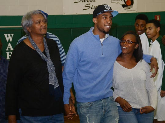 Brooklyn Nets guard and former Peabody star Markel Brown (center) walks with his grandmother Jerri Mae Eggins (left) and sister Moryia Brown during a ceremony held Feb. 17 at Peabody Magnet High School where his jersey was retired.