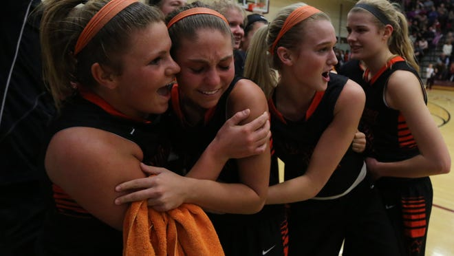 Hannah Fuller, left, and Whitney Fuller share a hug with teammates after outlasting Dowling for the win Friday. Valley won 59-58 on the road.