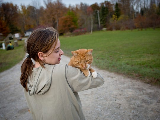 Jazmyne Simpson, 12, carries one of the family cats,