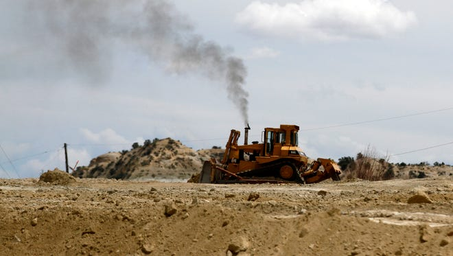 A bulldozer moves dirt July 14 during preparation work for the new truck bypass route south of Aztec.