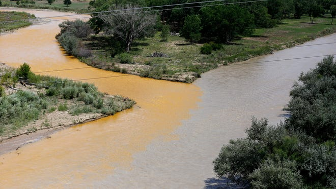Discolored water from the Animas River mixes with the San Juan River on Aug. 8, 2015, in the aftermath of the Gold King Mine spill.