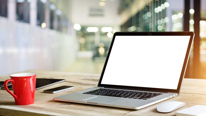 Laptop with blank white screen on table in office background