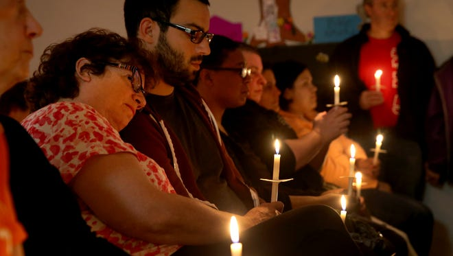 """Marsha Raines rests her head on the shoulder of her son, Larry Gersz, at a vigil held at Open Arms Community Church. """"I couldn't stay at home tonight."""" Raines said."""