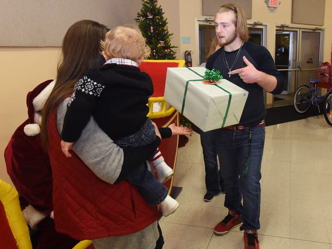 Lucas Johnson helps a family with their presents at
