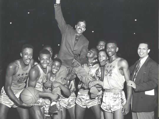 Attucks players, including Oscar Robertson (second from left) hoist coach Ray Crowe on their shoulders after winning the 1955 state title.